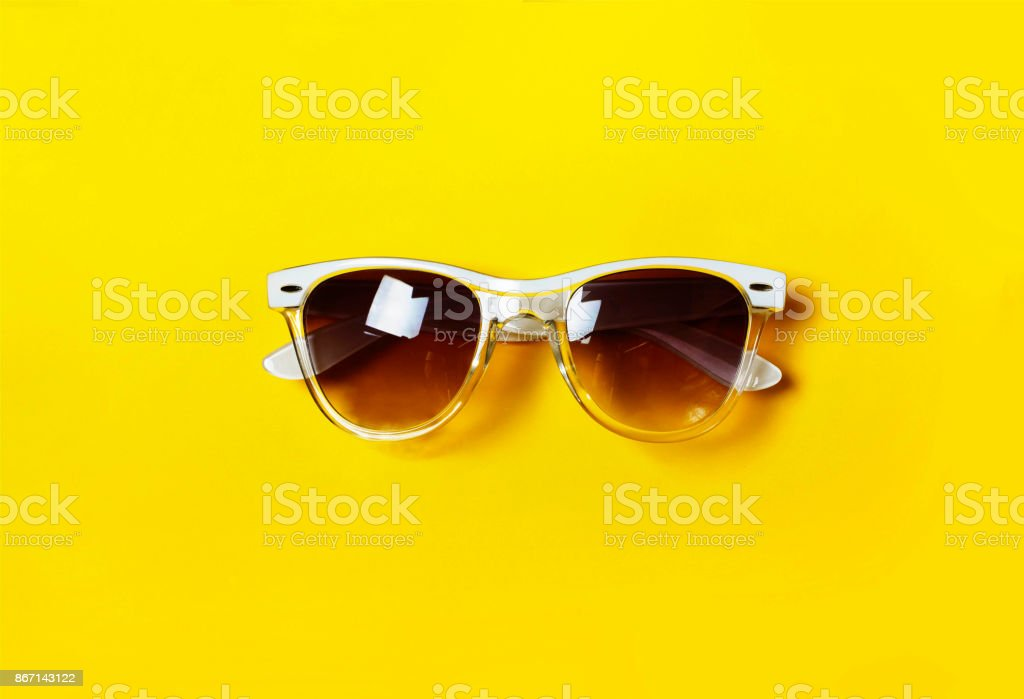 Hipster glasses.The concept of minimalism. White frame. Yellow background. stock photo
