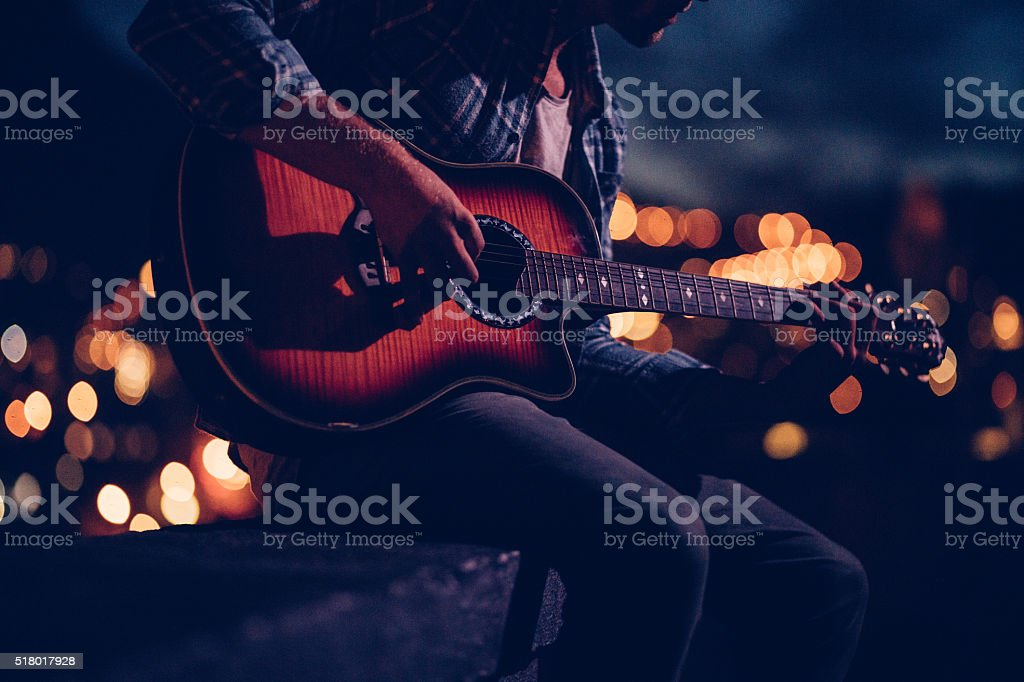Hipster guitarist playing on a rooftop at night stock photo