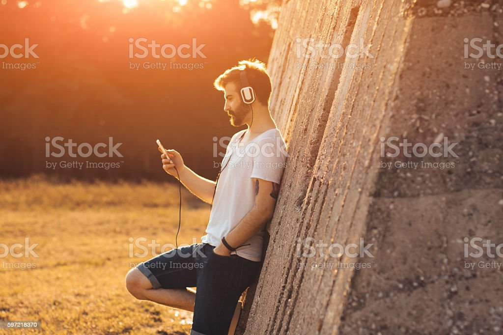 Hipster guy listening to music stock photo