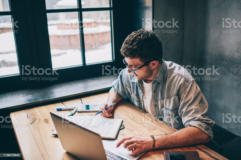Hipster Kerl grübelt über Idee für Essay sitzen am Holztisch mit Laptop-Gerät und Blick auf Lehrbuch, intelligente männliche Freiberufler verbringen Zeit für Fernarbeit denken über Geschäft in Innenräumen - Lizenzfrei Lernender Stock-Foto