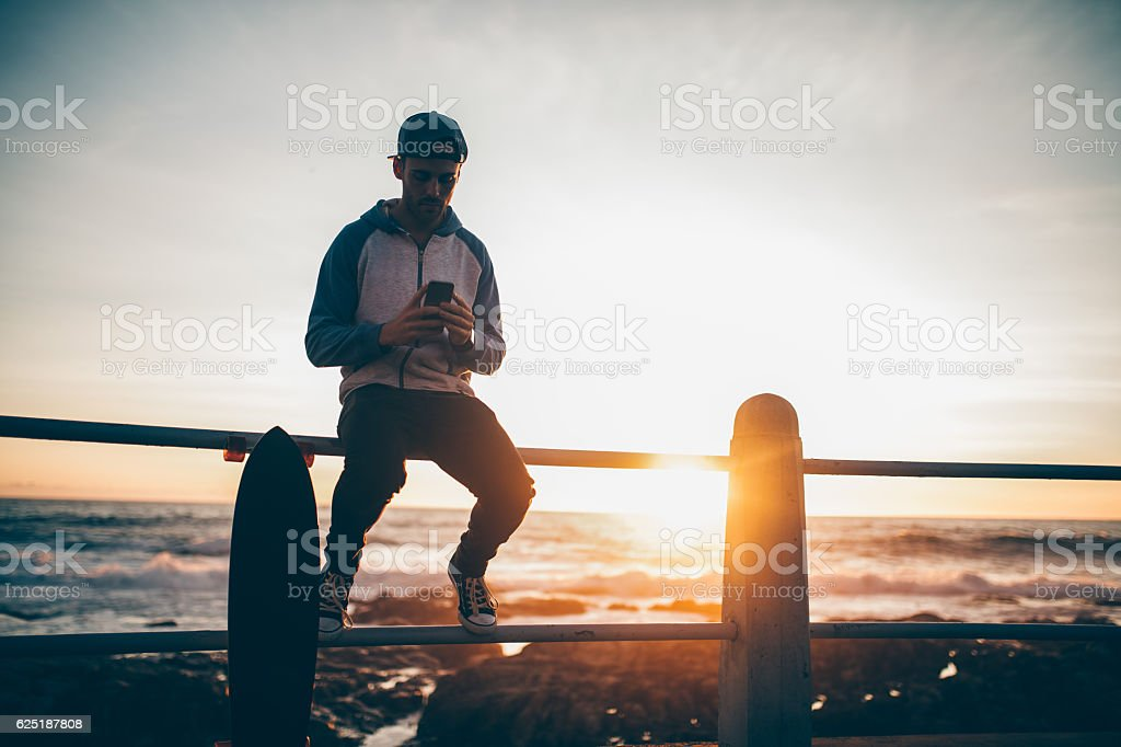 Hipster guy sitting on railing browsing with his smart phone stock photo