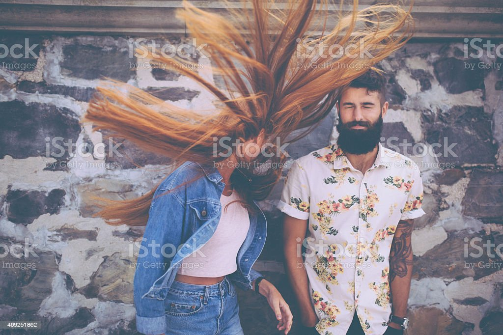 Hipster guy with hipster girl flinging her hair wildly stock photo