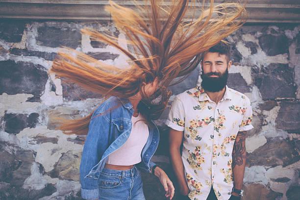 hipster mann mit hipster mädchen flinging ihr haar wilden - ehepaar tattoos stock-fotos und bilder