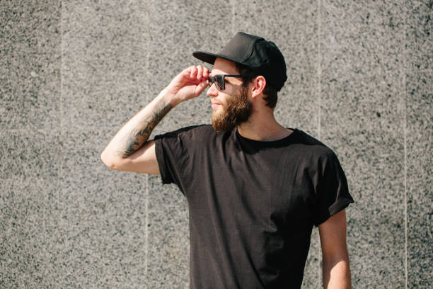 Hipster handsome male model with beard  wearing black blank baseball cap with space for your logo stock photo