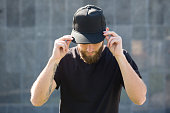 istock Hipster handsome male model with beard  wearing black blank baseball cap with space for your logo 858160872