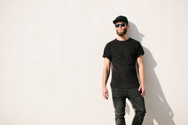 Hipster handsome male model with beard  wearing black blank  t-shirt with space for your logo or design in casual  style stock photo