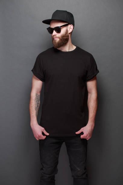 modelo masculino bonito de hipster com barba, vestindo camiseta preta em branco, com espaço para seu logotipo ou desenho sobre fundo cinza - camiseta preta - fotografias e filmes do acervo