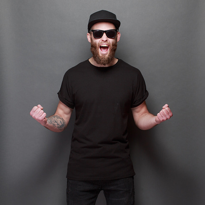 istock Hipster handsome male model with beard wearing black blank t-shirt with space for your logo or design over gray background 925775624