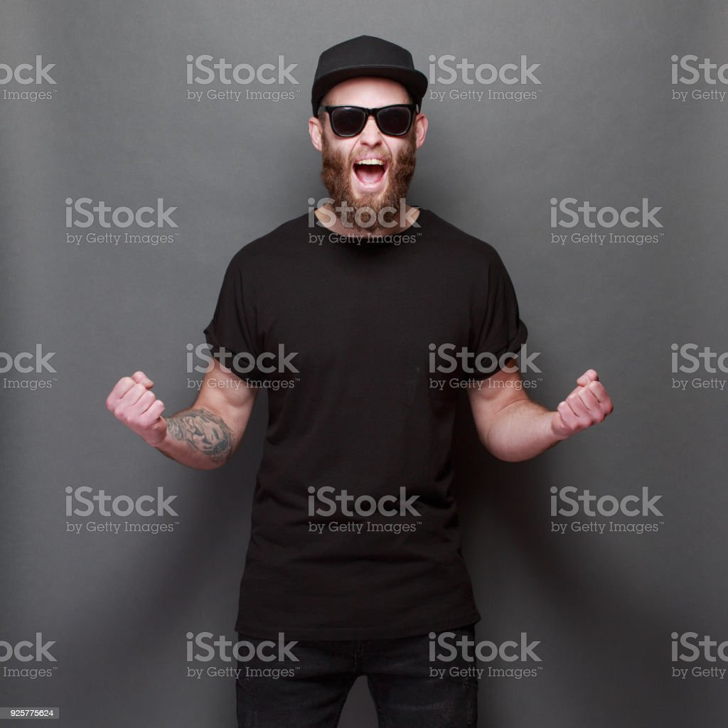 Hipster handsome male model with beard wearing black blank t-shirt with space for your logo or design over gray background stock photo