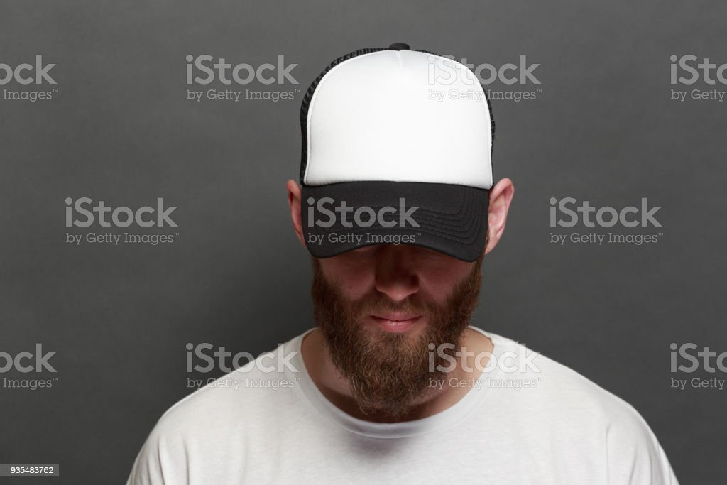 Hipster handsome male model with beard wearing white blank t-shirt and a baseball cap with space for your logo or design in casual urban style stock photo