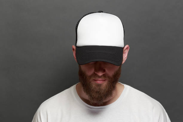 hipster handsome male model with beard wearing white blank t-shirt and a baseball cap with space for your logo or design in casual urban style - czapka zdjęcia i obrazy z banku zdjęć