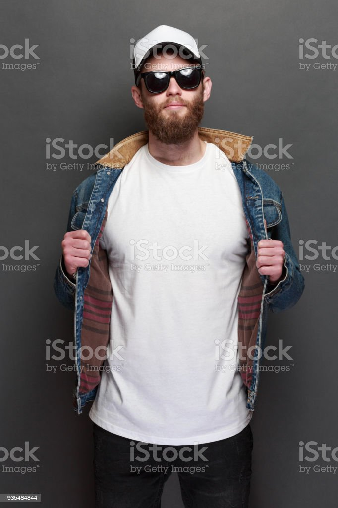 38fac287ae0da Hipster handsome male model with beard wearing white blank t-shirt and a baseball  cap with space for your logo or design in casual urban style - Stock image .