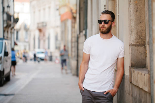 Hipster handsome male model with beard wearing white blank t-shirt with space for your logo or design in casual urban style Hipster handsome male model with beard wearing white blank t-shirt with space for your logo or design in casual urban style alternative pose stock pictures, royalty-free photos & images