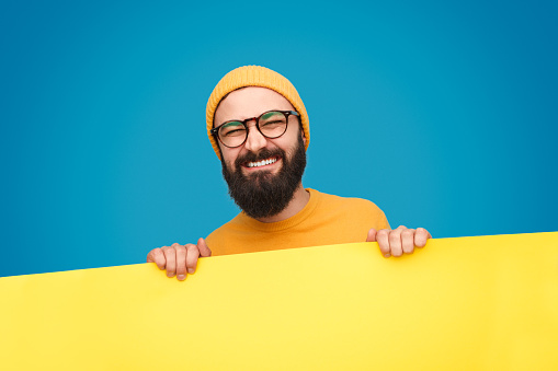 istock Hipster holding heavy banner with grimace 1136668120