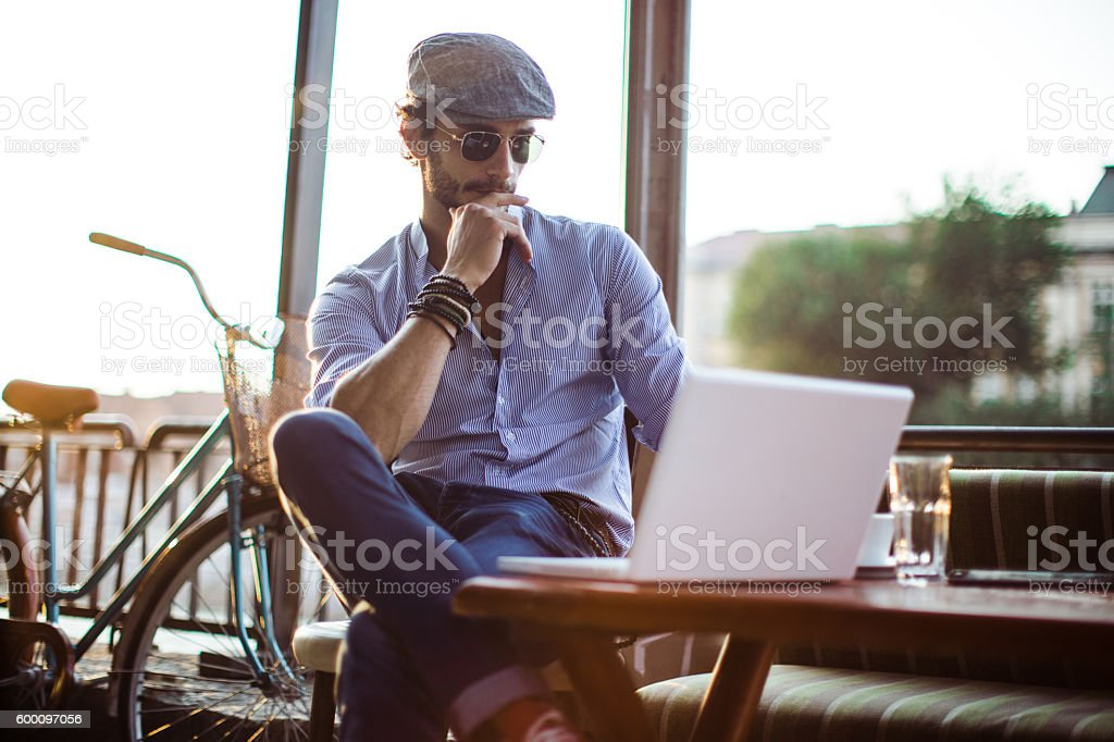 Hipster in cafe on laptop stock photo