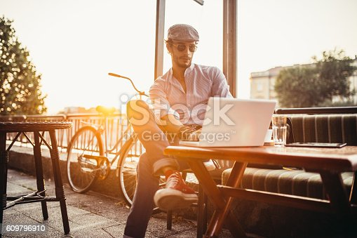Handsome young hipster sitting in a cafe and working on laptop