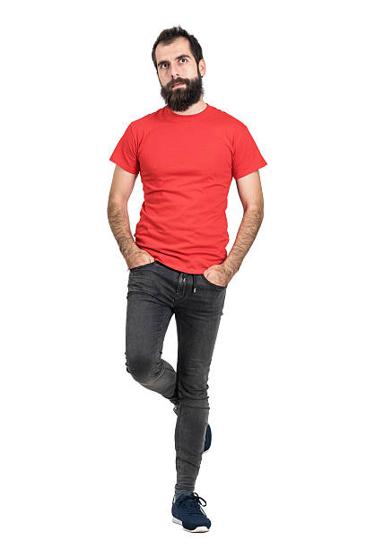 Hipster in red t-shirt standing and balancing on one leg Bearded hipster in red t-shirt standing and balancing on one leg looking away. Full body length portrait isolated over white studio background. men in tight jeans stock pictures, royalty-free photos & images