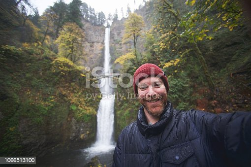 A Caucasian male 40-44 years with a red beard taking a selfie photographing of himself personal perspective at the Multnomah Falls Columbia River Gorge Portland Oregon USA in the rain