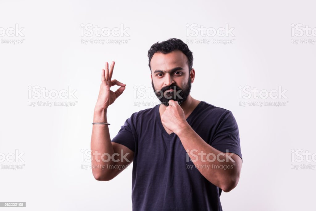 hipster indian young man with beard and mustache showing success sign or thumbs up with both hands, isolated over white background stock photo