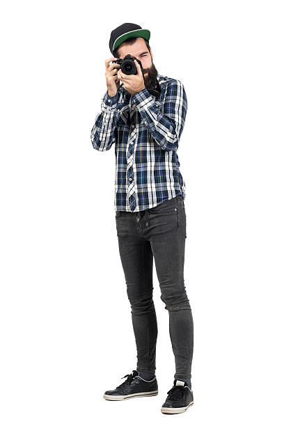 Hipster intaking photo with dslr camera looking at camera Hipster in plaid shirt taking photo with dslr camera looking at camera. Full body length portrait isolated over white studio background men in tight jeans stock pictures, royalty-free photos & images