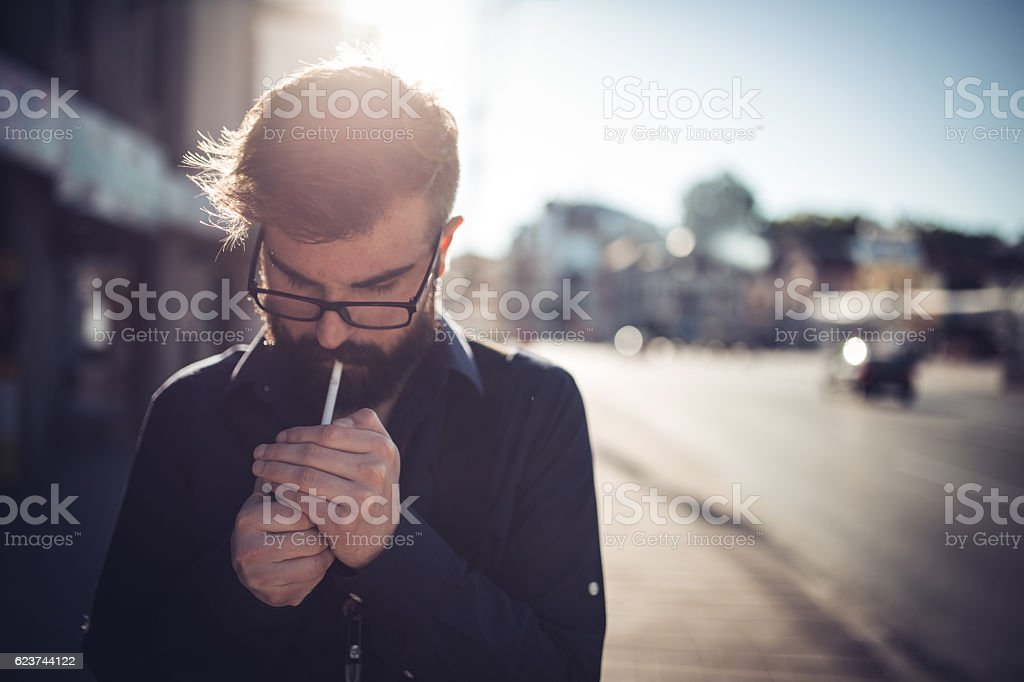 Hipster lighting a cigarette stock photo