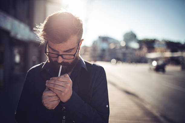 Hipster lighting a cigarette Young man lighting a cigarette on the street,front view smoking issues stock pictures, royalty-free photos & images