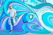 Hipster male with sunglasses and mobile phone next to wall of colorful  graffiti in Belgrade
