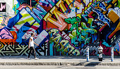 Hipster male walking next to wall of graffiti in Brooklyn