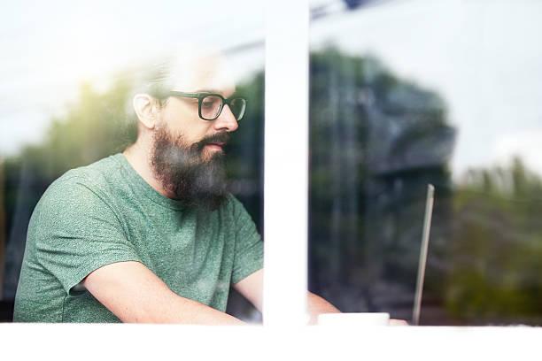 hipster mann hinter fenster, arbeiten auf laptop - geek t shirts stock-fotos und bilder