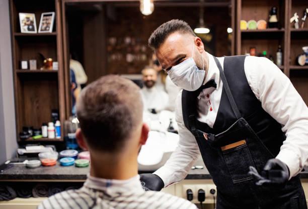 hipster man client een bezoek aan haidresser en hairstylist in kapper. - mirror mask stockfoto's en -beelden