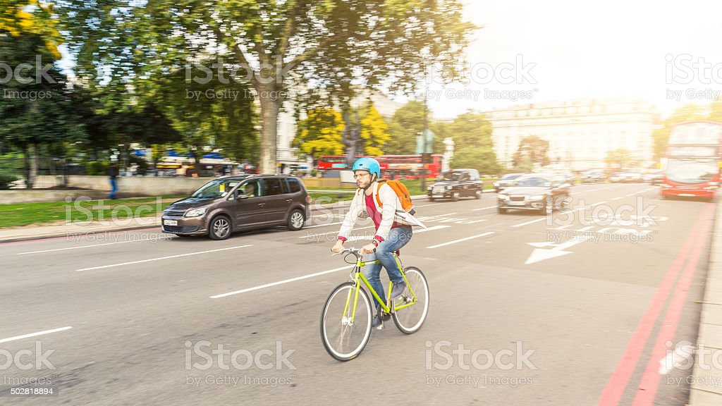 Hipster man cycling in London stock photo