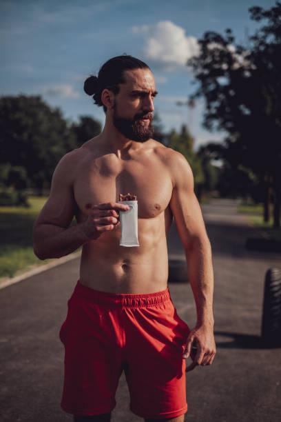 Hombre hipster comiendo barra de proteínas después de un entrenamiento duro - foto de stock