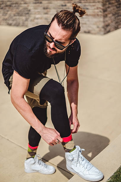 hipster man fixing his sock and looking to the side - hipster unterwäsche stock-fotos und bilder