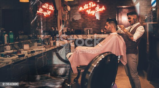 986804130istockphoto Hipster man getting haircut by barber in vintage barber shop 915640690