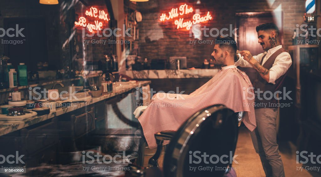 Hipster man getting haircut by barber in vintage barber shop - fotografia de stock