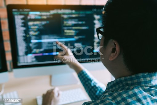 istock Hipster man hands pointing coding html and programming develop on screen computer. 1125593971