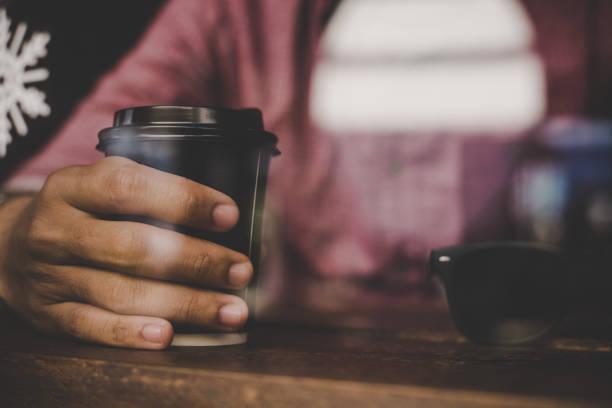 hipster-mann hält eine tasse kaffee und sitzt auf der café-bar. vintage farbstil. - www kaffee oder tee stock-fotos und bilder