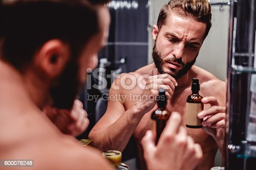 istock Hipster man holding bottle in the bathroom 600076248