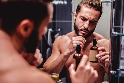 Hipster Man Holding Bottle In The Bathroom - Fotografie stock e altre immagini di Addetto alle pulizie