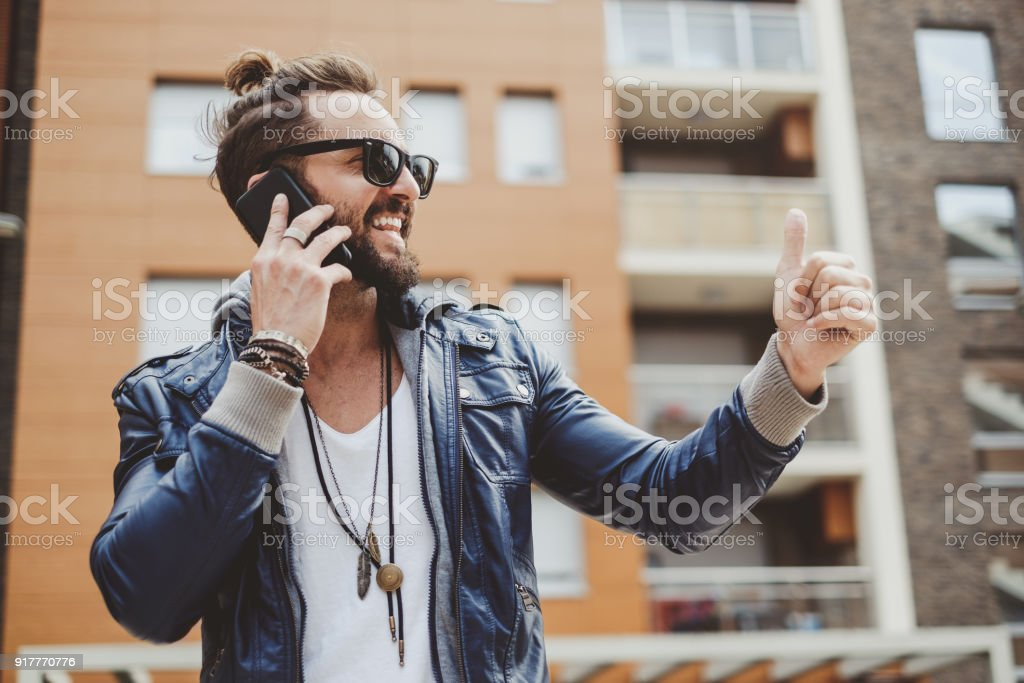 Hipster man holding thumb up while talking on the phone stock photo