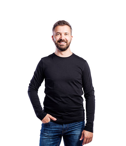 Hipster man in black long-sleeved t-shirt, studio shot, isolated Young handsome hipster man in black long-sleeved t-shirt, hand in pocket, studio shot on white background, isolated long sleeved stock pictures, royalty-free photos & images