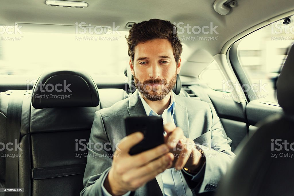 Hipster man in car Typing text message  on mobile phone stock photo