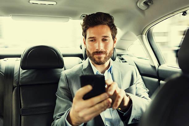 Hipster Mann im Auto Eingabe SMS auf Handy – Foto