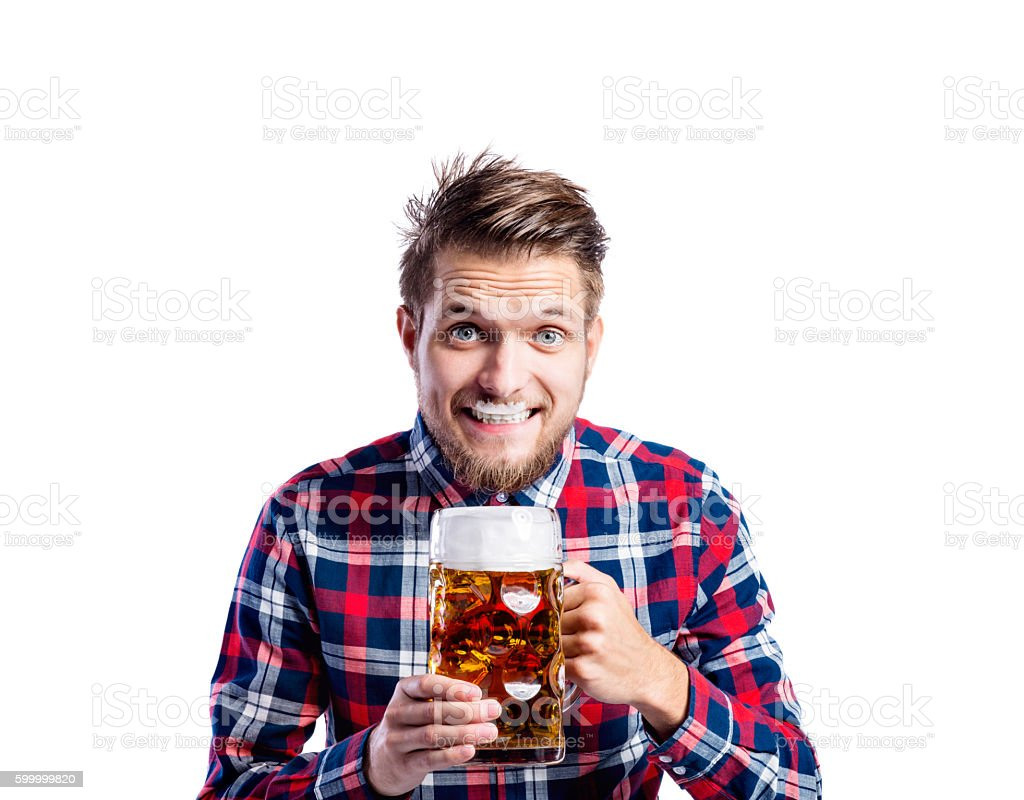 Hipster man in checked shirt drinking beer, studio shot stock photo