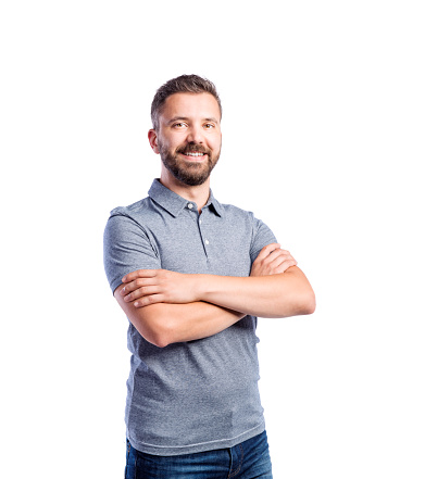 Young handsome hipster man in gray t-shirt, arms crossed, studio shot on white background, isolated