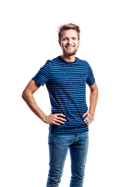 Hipster man in jeans and t-shirt, studio shot, isolated Hipster man in jeans and striped blue t-shirt, arms on hips, studio shot on white background, isolated akimbo stock pictures, royalty-free photos & images