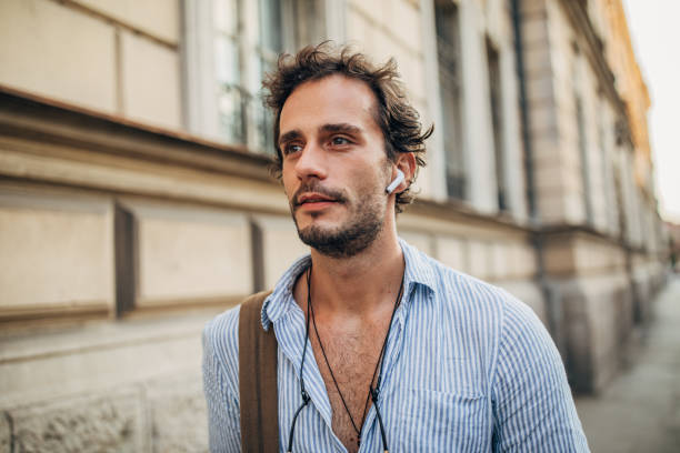 Hipster man in the city listening music on wireless headphones One hipster man walking in the city and listening music on wireless headphones wireless headphones stock pictures, royalty-free photos & images