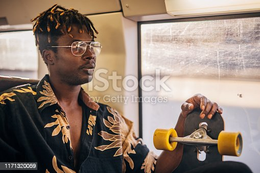 Young man sitting in the train and holding skateboard