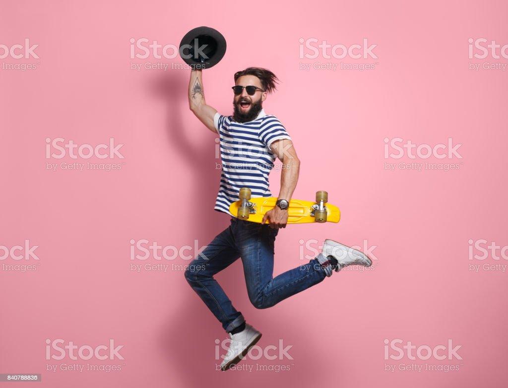 Homem hipster saltando com longboard - foto de acervo