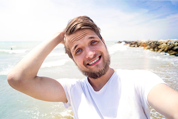 Hipster man on beach, smiling, taking selfie, sunny summer stock photo